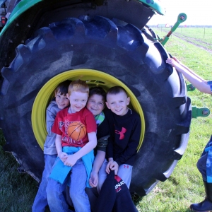 School children pose inside tractor wheel